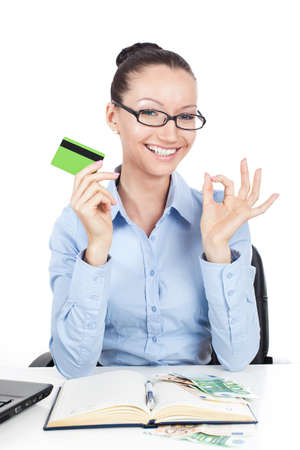 Smilling businesswoman on workplace with credit card in hand photo