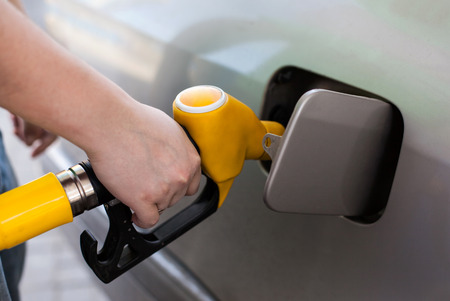 refilling: Driver pumping gasoline at the gas station, closeup Stock Photo