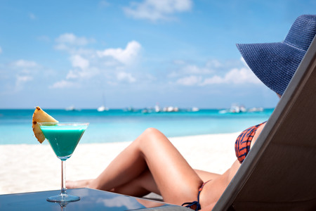 Woman in hat sitting in chaise longue with glass of cocktail
