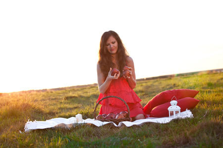 Girl with red apple in hands in red dress on summer fields photo