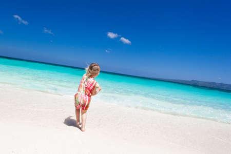 Happy little girl having fun on the beach  photo