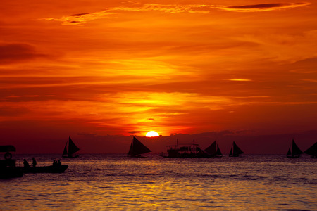 Sunset on tropical beach with sailng boats photo