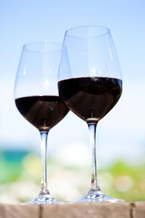 Two glasses with red wine, outside on nature background photo