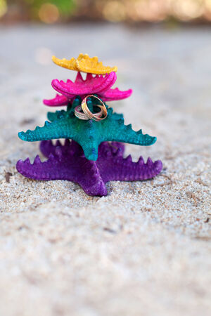 Gold wedding rings on color starfishes on white beach. Wedding Vacation concept photo