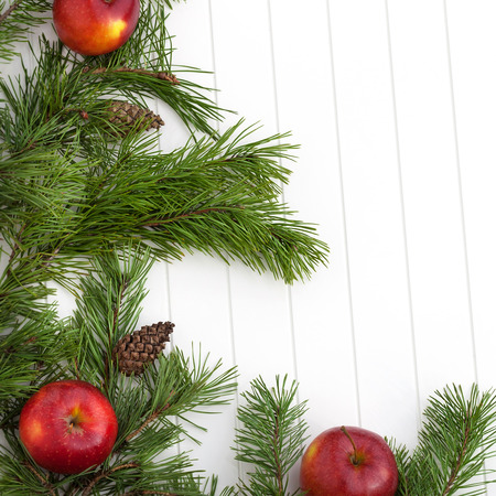 Decorated pine branches with cones and red apples on white wooden table,  free space photo