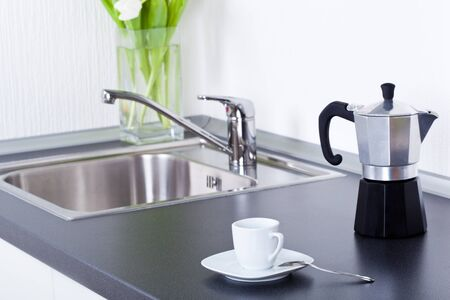 Coffeemaker and cup of coffee in kitchen interior photo