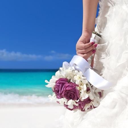 svatba: Svatební kytice v rukou nevěsty na pláži Reklamní fotografie