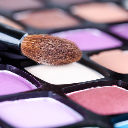 multicolored eye macro: Make-up eye shadows palette with makeup brush, closeup Stock Photo