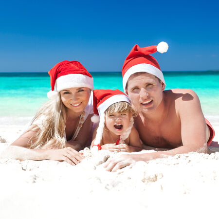 Family celebrating Christmas on beach in Santa hats photo