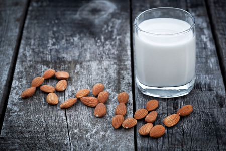 Almond milk, nuts and glass of tasty milk on old wooden table