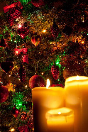 favours: Christmas candles on fir tree lights background