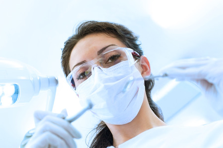 Dentist wearing surgical mask while holding angled mirror and drill, ready to begin photo