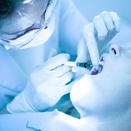 treating: Dentist treating a female patient