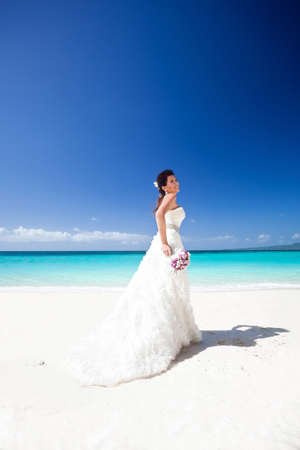 Beautiful bride in wedding gown with train, on white sandy beach, smiling and feeling happiness. Travel wedding concept. photo