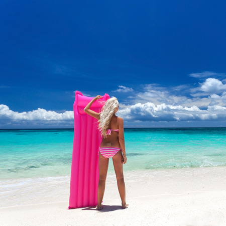 Woman with pink swimming mattress on tropical beach, looking to the sea photo