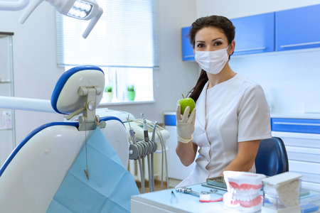 Dentist woman in mask at stomatology office holding green apple. Health care concept photo