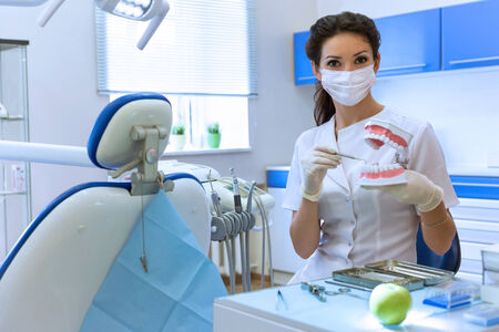 health care concept: Dentist woman in mask at stomatology office holding green apple. Health care concept Stock Photo