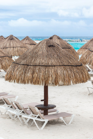 Sun umbrella and beds on caribbean beach in cloudy weather, Cancun, Mexico photo