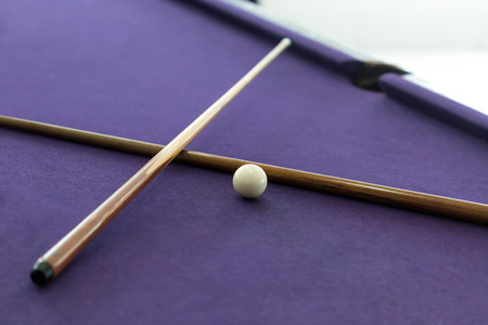 cues: Billiard cues and white ball in pool table Stock Photo