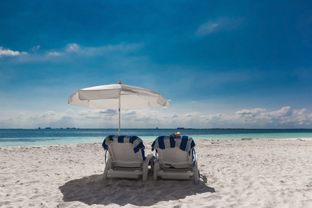 Caribbean beach with sun umbrella and beds, Cancun, Mexico photo