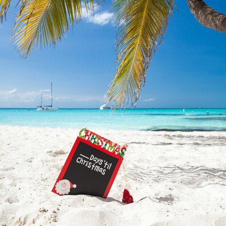 fill in: Christmas board on white sandy beach, with inscription - One day till Christmas, Tourism concept