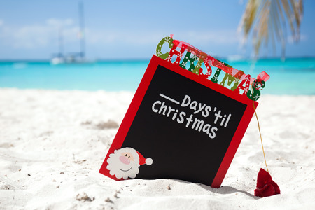 Christmas board on white sandy beach, with inscription - One day till Christmas, Tourism concept photo