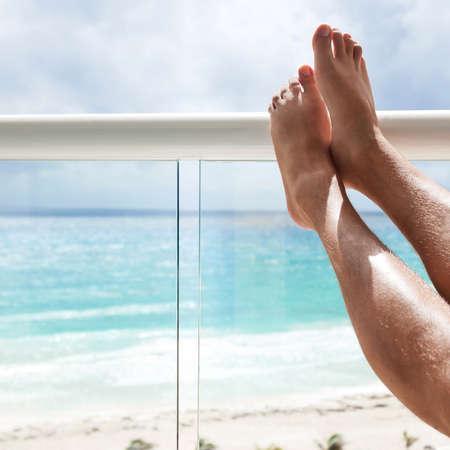 Male legs in hotel balcony over sea view, travel destination concept photo