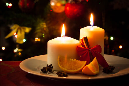 favours: Christmas decoration, candles, cinnamon sticks and pieces of orange, on christmas tree background