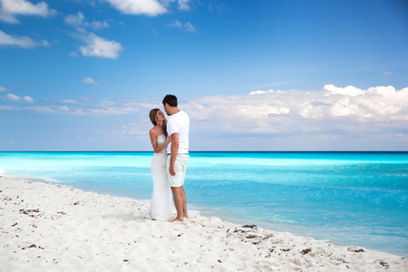 Bride and groom looking to each other and holding hands, romantic vacation at Caribbean beach photo