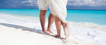 footsie: Close up male and female feet on white sand, kissing Stock Photo