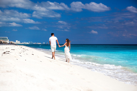 Young beautiful newlyweds in love holding hands and walking away on tropical sandy beach, back view photo