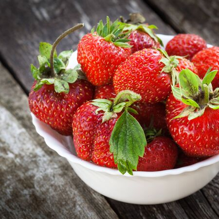 Fresh red strawberries in white bowl on old wooden table photo