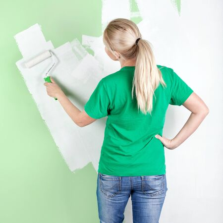 Full length portrait of  woman painting the wall Stock Photo
