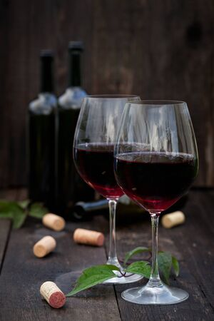 closed corks: Glasses of red wine with corks on old wooden table Stock Photo