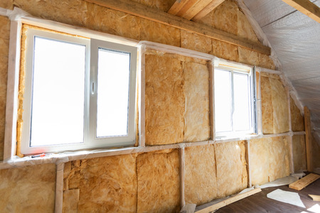 Inside wall heat isolation with mineral wool in wooden house,  building under construction Stockfoto