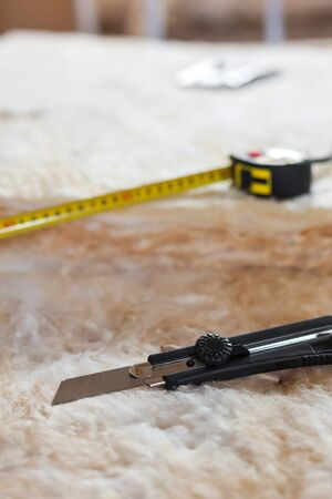 Measure tape and knife on mineral wool, closeup