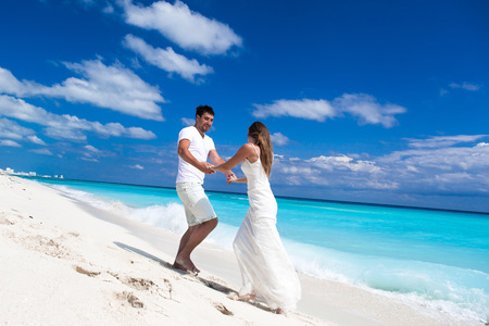 Happy newlyweds in white dresses having fun on beach with turquoise sea background photo