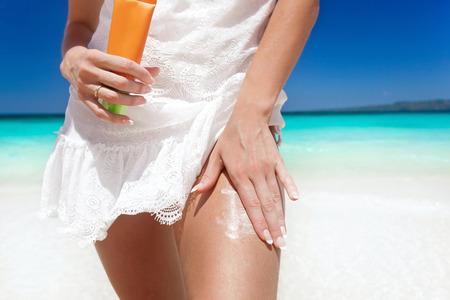 Portrait of woman holding sunscreen cream on beach, beauty concept photo