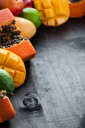 A lot of fresh exotic tropical fruits on wooden background with free copyspace photo