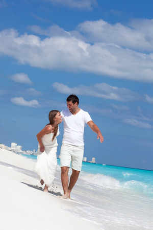 Young beautiful newlyweds in love holding hands and walking on tropical sandy beach photo