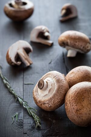 Fresh delicious portobello mushrooms decorated rosemary on wooden background photo
