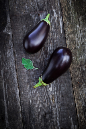 Tasty fresh eggplants on old wooden table, autumn harvest. photo