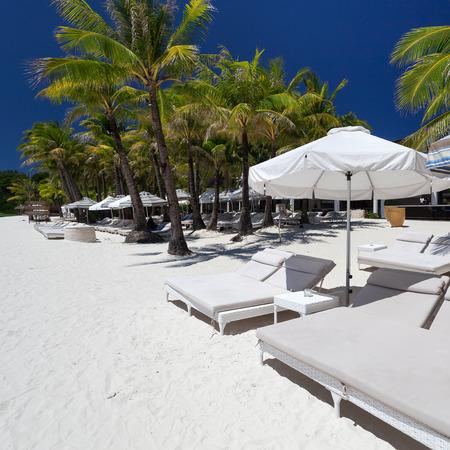 sun umbrellas: Sun umbrellas and beach beds on tropical coastline, Philippines, Boracay Stock Photo