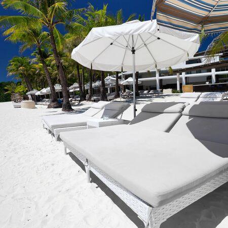 boracay: Sun umbrellas and beach beds on tropical coastline, Philippines, Boracay Stock Photo