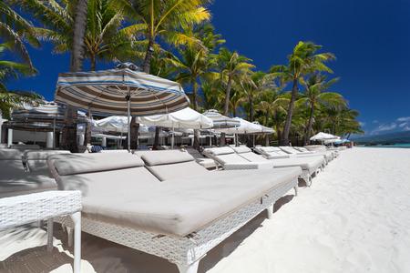 Sun umbrellas and beach beds on tropical coastline, Philippines, Boracay Stock Photo