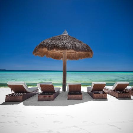 Sun umbrella and beach beds on tropical coastline, Philippines, Boracay photo