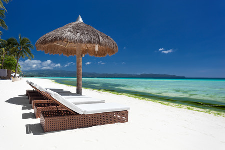 boracay: Sun umbrella and beach beds on tropical coastline, Philippines, Boracay Stock Photo