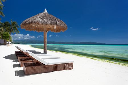philippines: Sun umbrella and beach beds on tropical coastline, Philippines, Boracay Stock Photo