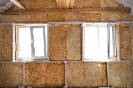 glasswool: Inside wall heat isolation with mineral wool in wooden house,  building under construction Stock Photo