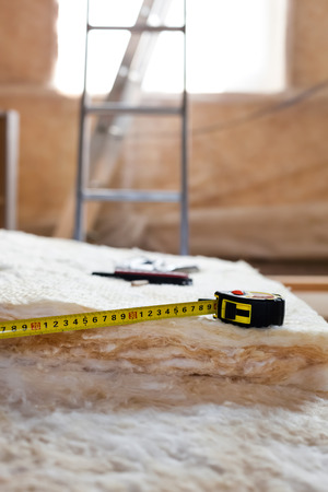 Measure tape and knife on mineral wool, closeup photo
